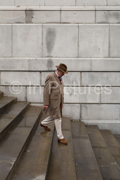 A smartly-dressed gentleman carefully descends steps beneath the Fourth Plinth, in Trafalgar Square, Westminster, on 9th April 2019, in London, England.