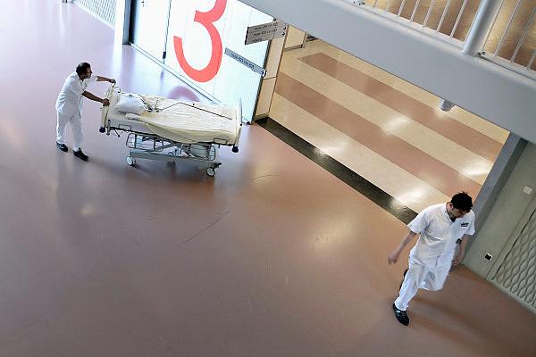 Nederland, Nijmegen, 3-9-2013Ziekenhuismedewerker,  verplaatst een bed door een gang in het umc radboud, radboudumcFoto: Flip Franssen