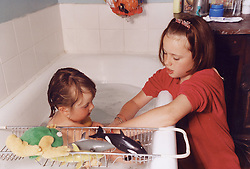 Young carer bathing baby in bath,