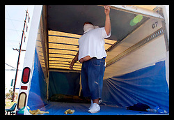 8th Sept, 2005. Hurricane Katrina aftermath. New Orleans. Corpses are finally retrieved from Methodist hospital  in East New Orleans and are loaded into the back of an unrefrigerated truck by private contractors with little to no protection. 8 corpses were already in the truck and another 5 were added. The contractor wears a T-shirt as a face mask. The stench was almost unbearable.