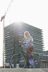 Low angle view of a teenage girl riding a bicycle, Munich, Bavaria, Germany