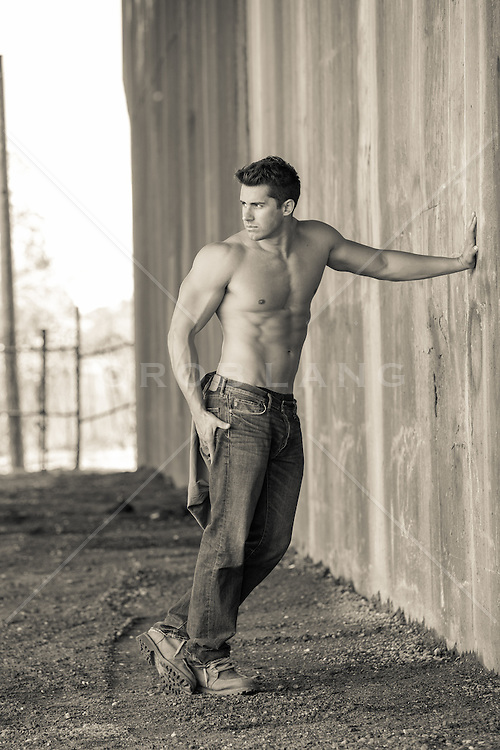 shirtless muscular man leaning on a wall