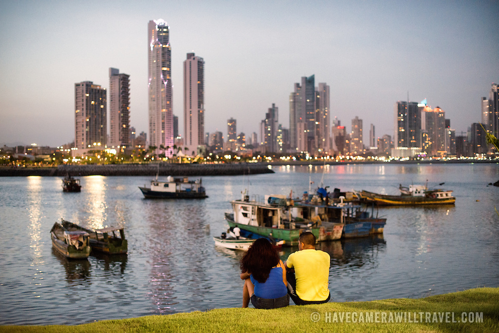 A couple enjoys the view on a summer evening in Panama City, Panama, with the modern skyscrapers of Punta Paitilla forming a cityscape in the background, with the traditional wooden fishing boats of Panama City in the foreground. on the waterfront of Panama City, Panama, on Panama Bay.