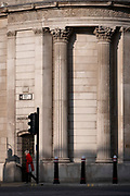 An elderly woman walks beneath the tall columns of the Bank of England, at the corner of Threadneedle and Princes Streets in the City of London, on 1st March 2021, in London, England.
