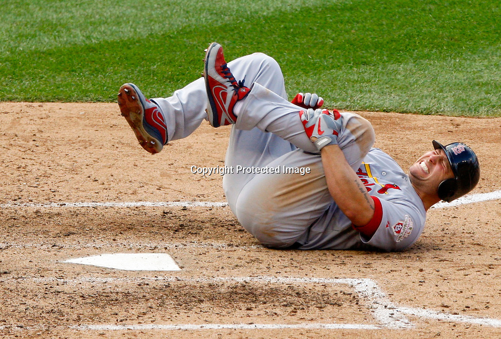 St. Louis Cardinals' Matt Holliday grimaces after fouling a ball of his leg against the Washington Nationals during the eighth inning in Game 3 of their MLB NLDS baseball series in Washington.