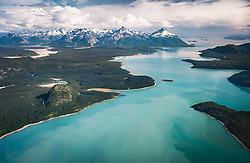 """The Muir Inlet of the East Arm of Glacier Bay in Glacier Bay National Park and Preserve offers some of the best sea kayaking in the park. The turquoise color of the water is caused by the minerals contained in """"rock flour;"""" the material that tidewater glaciers release as the glaciers grind rocks into dust on their way to the sea. This aerial view is looking south, down the Muir Inlet. Pictured are: The Nunatak and Nunatak Cove (left foreground); Westdahl Point (right foreground), Stump Cove, the entrance to Wachusett Inlet; Hunter Cove, Rowlee Point, Point McLeod (middle right); Sealers Island (enter); Maquinna Cove (center background); Adams Inlet (center background to left background); Tree Mountain, Mount Case, Mount Right; Garforth Island, Sturgess Island, North Marble Island, South Marble Island, Willoughby Island, the northernmost islands of the Beardslee Island (upper right background); Sitakaday Narrows and the entrance to Glacier Bay (furthermost upper right background).<br /> <br /> Glacier Bay National Park and Preserve is located in southeast Alaska. Known for its spectacular tidewater glaciers, icefields, and tall costal mountains, the park is also an important marine wilderness area. The park a popular destination for cruise ships, is also known for its sea kayaking and wildlife viewing opportunities. <br /> <br /> Glacier Bay National Park is home to humpback whales which feed in the park's protected waters during the summer, both black and grizzly bears, moose, wolves, sea otters, harbor seals, steller's sea lions and numerous species of sea birds. <br /> <br /> The dynamically changing park, known for its large, contiguous, intact ecosystems, is a United Nations biosphere reserve and a UNESCO World Heritage site. The effects of a warming climate are easily seen here. It is a place where can you witness geological change firsthand — change that is normally measured in millennia."""