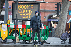 © Licensed to London News Pictures. 30/12/2020. London, UK. Members of the public walk past a Covid-19 information display in Hammersmith, as the Oxford vaccine is approved for use with the UK ordering 100 million doses. Ministers are expected to roll out vaccinations from the 4 January 2021 as they mull over putting parts of the country into tier 5 restrictions to slow the spread of the latest Covid mutation which has increased infections in the capital. Last week Health Secretary Matt Hancock announced another new Covid-19 mutation has been discovered in the UK as Downing Street ordered many more areas of England to go into Tier 4 lockdown with tougher new Covid-19 restrictions for many as the mutated strains continue to spread throughout the UK. Photo credit: Alex Lentati/LNP