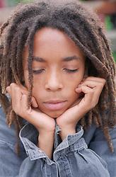 Teenage boy holding head in hands looking unhappy,