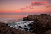 Pacific Ocean waves crash into a narrow, rocky inlet at Lovers Point in Pacific Grove, California.