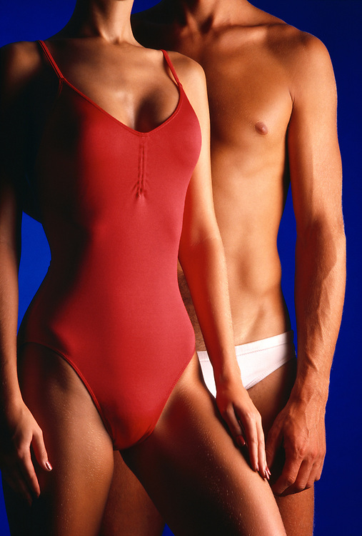Anonymous couple displaying fit, tan and beautiful bodies wearing red and white swimsuits