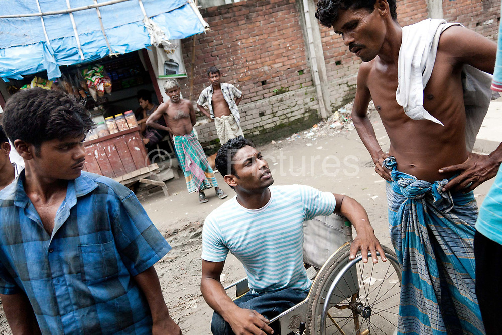 Dhaka, Bangladesh. Ibrahim, wheel chair bound and a former beggar and street kid, now working for CSID as peer educator rolling along a dirt road in Dhaka in his wheel chair.The Stars Foundation visiting CSID. Centre for Services and Information on Disability (CSID) is a charity working for integrating disabled children into mainstream society.