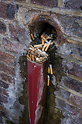 Discarded cigarettes spill from a hole in a brick wall in Waterloo, south London. We see a detail view of the butt that have been left in the gap of this Victorian wall opposite a bus station. Travellers leave their cigarette ends where others have too.