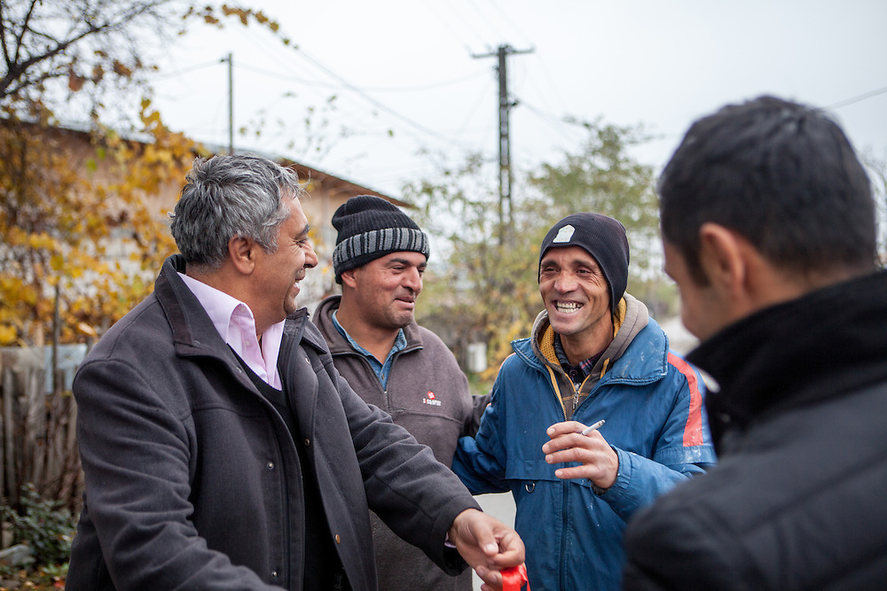 Roma activists Marius and Gheorghe Tudor chatting on a Saturday morning with Dan and Laurentio - two young Roma reconstruction workers on the way to their building site in Marginenii de Jos.