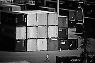 A man is walking next to a pile of containers in the port authority of Danang, Vietnam, Asia