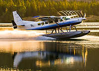An Alkan Air Ltd. Cessna 208 reflects off Schwatka Lake and departs into the dawn of a new day.