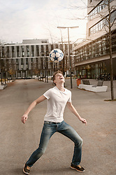 Teenage boy playing football in town, Bavaria, Germany