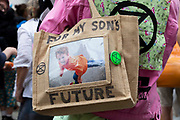 At a climate demonstration held by Extinction Rebellion, one activist has a picture of her son on a carrier bag with the words for my sons future written across it and XR badges pinned to it on 27th August, 2021 in London, United Kingdom. The activist group Extinction Rebellion XR are planning actions of disruption for two weeks straight beginning on August 23rd, 2021 in an effort to bring awareness and priority to the global climate emergency in advance of the COP 26 Summit which will be held in Glasgow later this year.