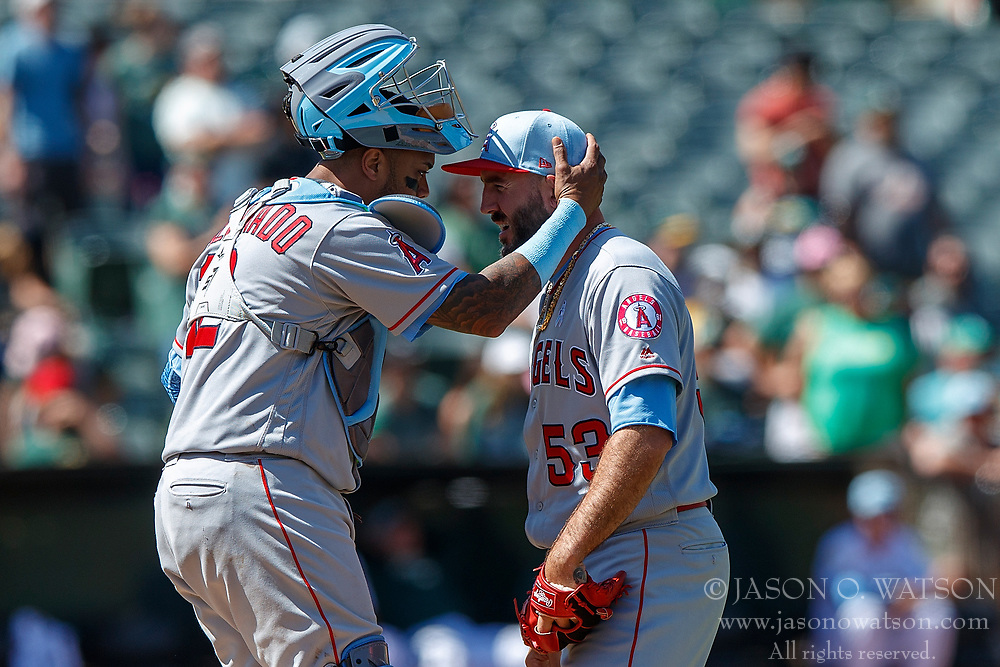 OAKLAND, CA - JUNE 17: Martin Maldonado #12 of the Los Angeles Angels of Anaheim talks to Blake Parker #53 during a mound visit during the ninth inning against the Oakland Athletics at the Oakland Coliseum on June 17, 2018 in Oakland, California. The Oakland Athletics defeated the Los Angeles Angels of Anaheim 6-5 in 11 innings. (Photo by Jason O. Watson/Getty Images) *** Local Caption *** Martin Maldonado; Blake Parker