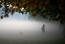 © Licensed to London News Pictures. 27/09/2018. London, UK. A woman walks her dog during misty weather in Hyde Park at sunrise this morning. The temperature in the capital is set to reach 22 degrees Celsius later today. Photo credit : Tom Nicholson/LNP