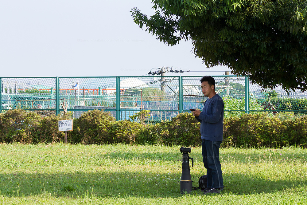 A Japanese man with a large lens on his camera waits in a park to photography military aircraft flying in to the nearby Atsugi airbase in Yamato, Kanagawa, Japan. Tuesday May 1st 2018