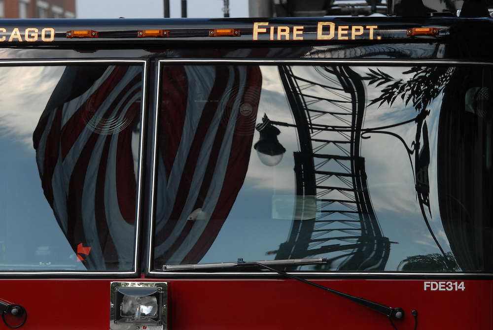 An American flag and ladder are reflected in the windshield of a Chicago Fire Department vehicle on W. Roosevelt Road during a Memorial Day procession and mass commemorating the service of firemen and the military at Holy Family Church.