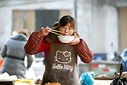 A woman wearing a Hello Kitty apron eats a bowl of noodles at a market in Zhujiao Township, Chuzhou, Anhui Province, China on 02 March, 2011.  Chuzhou is the city where Dongdaxu Village is located, the ancestral home of current Chinese vice premier Li Keqiang, slated to be the next premier and the man in charge of China's economic transformation