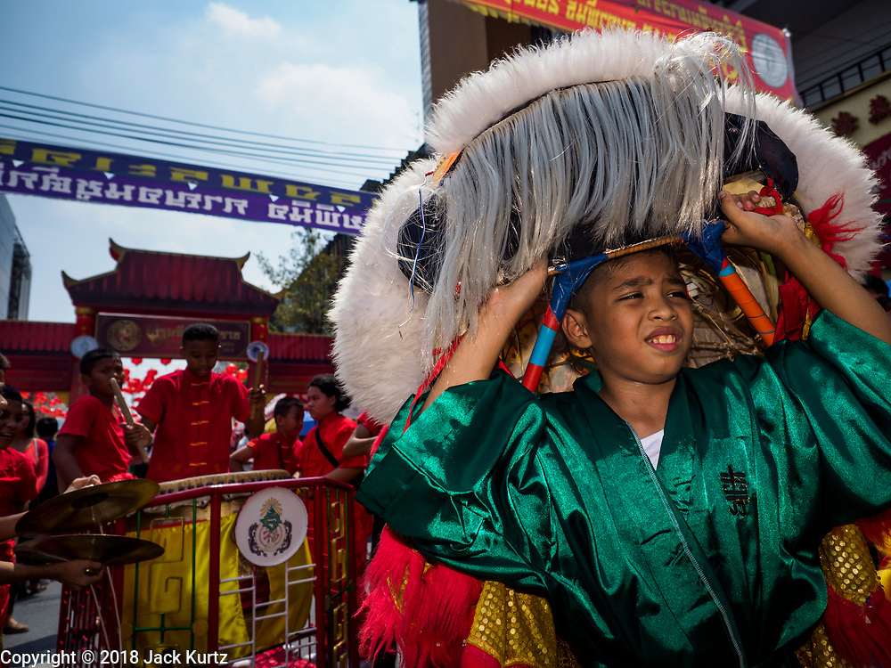 16 FEBRUARY 2018 - BANGKOK, THAILAND: A lion dancer relaxes on Yaowarat Road during Chinese New Year celebrations in the Chinatown neighborhood of Bangkok. Thailand has a large Chinese community and Lunar New Year is widely celebrated, especially in larger cities. This will be the Year of the Dog.      PHOTO BY JACK KURTZ