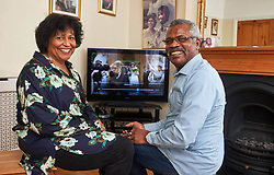 """EXCLUSIVE: SILVER SCREEN - MEET THE HUSBAND AND WIFE COUPLE WHO RETIRED AND DECIDED TO BECOME MOVIE STARS WITH PIX By Magnus News Agency Meet the husband and wife who decided when they retired to try something new in life - so they became MOVIE STARS. Gilbert Newton, 73, and wife Joy, 63, have been married since 1978 but never once imagined they'd be rubbing shoulders with Hollywood greats in their golden years. The couple have worked on nearly 100 films, TV shows, commercials and promotions since signing up to become extras. Far from slowing down, now one or the other of the pair is usually working on something seven days a week and they can be up at 4am to travel to location for filming. Gilbert, a former sales executive, and Joy, a former teacher, from London, say they both love their new jobs so much they don't have any time for the usual hobbies of retirement. Gilbert has appeared on screen in films such as Genius, Florence Foster Jenkins and Kingsman: The Golden Circle and Joy has graced screens on the biggest show on earth appearing in American football Super Bowl advert in 2017. Gilbert said: """"The first film I went for was Genius with Colin Firth and Jude Law. The agent gave me the details and booked me there and I arrived. """"It's was a completely new experience and nothing like I'd done before, but people were very nice, I've worked with nice people in the past but in a different industry, and with the extra work everyone is nice to you and saying you look good on screen and that sort of thing. """"And I was featured in the film, I didn't realise at first, but this was my first film and I got some screen time. """"Jude Law and Colin Firth were the actors on the day, we stand pretty close to each other in a lot of the scenes. We're not supposed to go up and speak to the actors because they've got things going on in their head and they don't want to be distracted. """"It was in a nightclub supposed to be in New York, but it was in London som"""