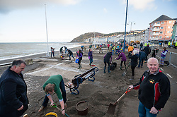 © Licensed to London News Pictures. 11/01/2014. Aberystwyth, UK The clean up operation continues  in Aberystwyth after the extreme weather severely damaged the promenade.  Hundreds of volunteers of all ages armed with shovels, spades and buckets join forces to help clean the tons of sand and debris off the battered promenade at Aberystwyth on the west Wales coast.  The estimated cost of the repairs to the promenade currently runs into the millions of pounds, with much uncertainty over where the funding will come from. Photo credit : keith morris/LNP
