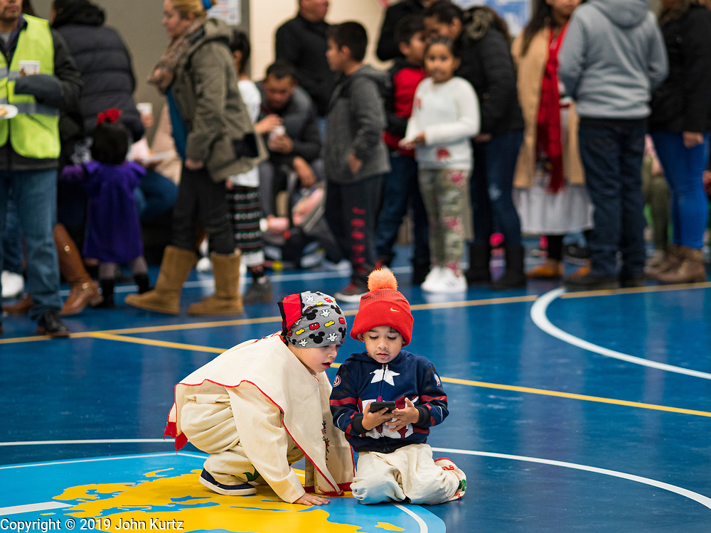 11 DECEMBER 2019 - DES MOINES, IOWA: Boys dressed as Juan Diego, the indigenous Mexican peasant,  look at a smart phone during the Virgin of Guadalupe celebration at Our Lady of the Americas Catholic Church in Des Moines. Virgin of Guadalupe Day is one of the most important holy days in Mexican Catholicism. It marks Dec. 12, 1531, the day Juan Diego, an indigenous Mexican peasant, saw an apparition of the Virgin Mary on a barren hillside in what is now Mexico City. A basilica was built on the site. Virgin of Guadalupe Day is celebrated throughout Mexico and in Mexican communities in the United States.               PHOTO BY JACK KURTZ