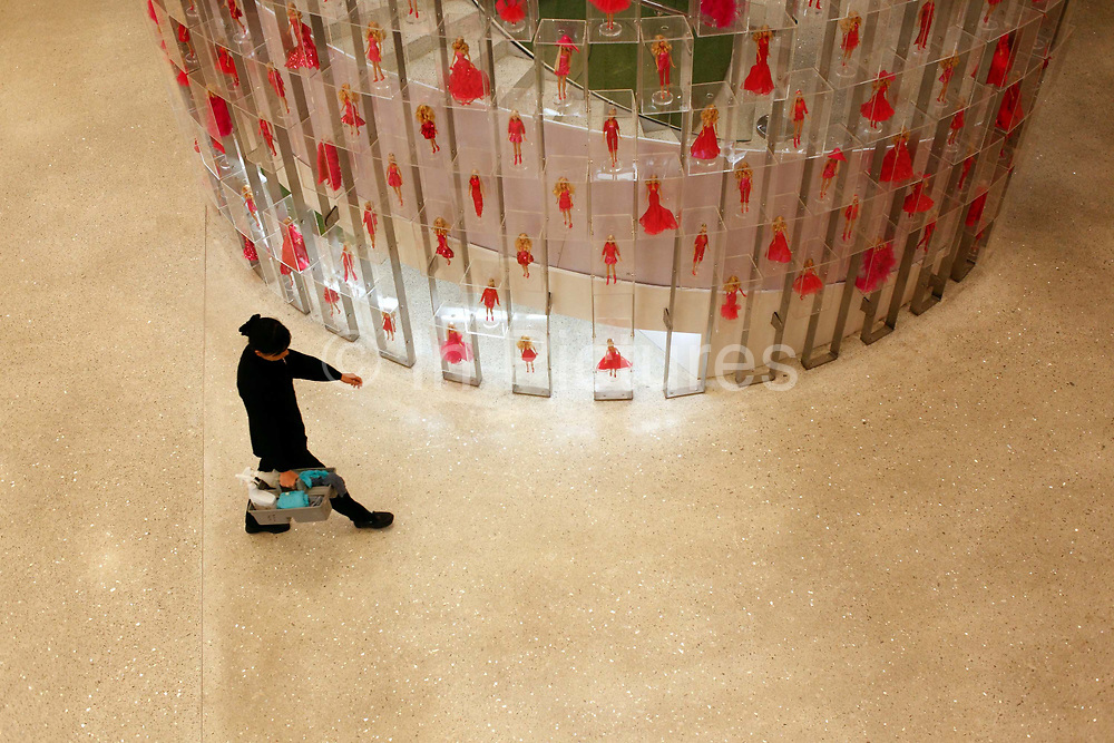 An emplyee walks past a wall of Barbie dolls during the Media Sneak Preview of the new Barbie Shanghai flagship store in Shanghai, China on 20 February 2009.  The Barbie store has become a hit in Shanghai as a place where doting mothers take their daughters, often the only child in the family, for a girls' day out.