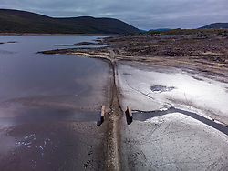 Garve ,Scotland, UK. 30th August 2021.Low water levels in Loch Glascarnoch reservoir near Garve have revealed structures previously hidden, including an old road, bridge, and telegraph polls.  The old road was the main route from Ullapool to Dingwall until the current new road was built alongside the reservoir.  The reservoir in Glen Glascarnoch was formed in the 1950s as part of the Conon hydro electric scheme.  Iain Masterton/Alamy Live News.