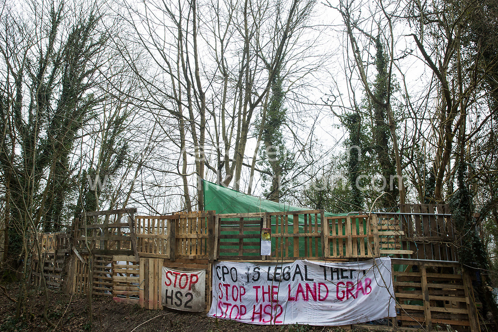 Wendover, UK. 20th February, 2021. A banner criticising the use of compulsory purchase orders hangs from the exterior of the Wendover Active Resistance Camp which is occupied by activists opposed to the HS2 high-speed rail link from HS2 Rebellion. A chain of such camps has been built by environmental activists along the planned route of the rail project from Euston in London to Birmingham.
