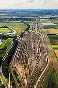 Nederland, Zuid-Holland, Zwijndrecht, 15-07-2012; Kijfhoek, rangeerterrein voor goederentreinen. Overzicht van de verdeelsporen (richting Barendrecht)..Kijfhoek huisvest Keyrail, exploitant Betuweroute en is in beheer bij ProRail. De Betuweroute, die begint als Havenspoorlijn op de Maasvlakte, verbindt via Kijfhoek de Rotterdamse haven met het achterland. Het rangeeremplacement dient voor het sorteren van goederenwagons waarbij gebruik gemaakt wordt van de zwaartekracht, het 'heuvelen': de wagons worden de heuvel opgeduwd, bij het de heuvel afrollen komen ze, door middel van wissels, op verschillende verdeelsporen. Railremmen zorgen voor het automatisch remmen van de wagons. Na het heuvelproces staan de nieuw samengestelde treinen op aparte opstelsporen..Kijfhoek, railway yard used by ProRail and Keyrail (Betuweroute operator). Kijfhoek connects via the Betuweroute (beginning as Havenspoorlijn on the Maasvlakte), through the port of Rotterdam with the hinterland. The shunting yard for sorting wagons makes use of gravity. The new trains are assembled on separate tracks..luchtfoto (toeslag), aerial photo (additional fee required).foto/photo Siebe Swart