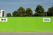 Green hoarding and trees around a construction site in the area under redevelopment near Station Square in the UK City of Culture 2021 on 23rd June 2021 in Coventry, United Kingdom. The UK City of Culture is a designation given to a city in the United Kingdom for a period of one year. The aim of the initiative, which is administered by the Department for Digital, Culture, Media and Sport. Coventry is a city which is under a large scale and current regeneration.
