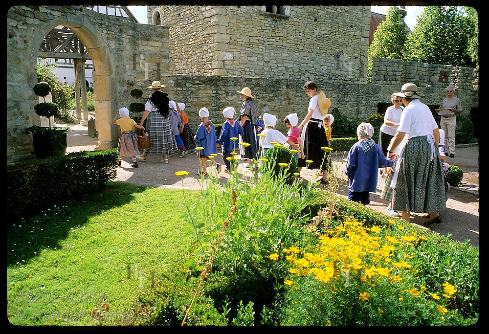 Schoolkids & women dressed as peasants visit gardens at Ecomusee folk museum; Ungersheim, Alsace. France