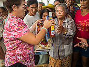 11 SEPTEMBER 2015 - BANGKOK, THAILAND: People receive rice and bottle of hot sauce during a food distribution for poor members of the community at Wat Kalayanamit in the Thonburi section of Bangkok. Food distribution is a common way of making merit in Chinese Buddhist temples. Wat Kalayanamit, a Thai Theravada temple, was founded by a Chinese-Thai family in the 1820s and observes both Thai and Chinese Buddhist traditions. The food distribution was not related to the temple's efforts to evict people living on the temple grounds, but many of the people at the food distribution live in the houses the temple plans to raze.    PHOTO BY JACK KURTZ