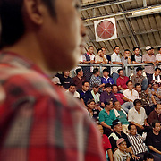 CHIANG MAI - MARCH 5 2006: The matches are held in all manner of buildings, from shanty shacks to upscale arenas. In the larger arenas, the winning purses can be $10,000 US or more, with bets raising the stakes even higher. Here an overflow crowd watches a match from stadium seating.  Bird Flu caused the banning of cock fights in 2005, but a persistent movement of Thai's claiming the social significance of the sport and a reduction in Bird Flu cases has allowed the fights to resume. (Photo by Logan Mock-Bunting)