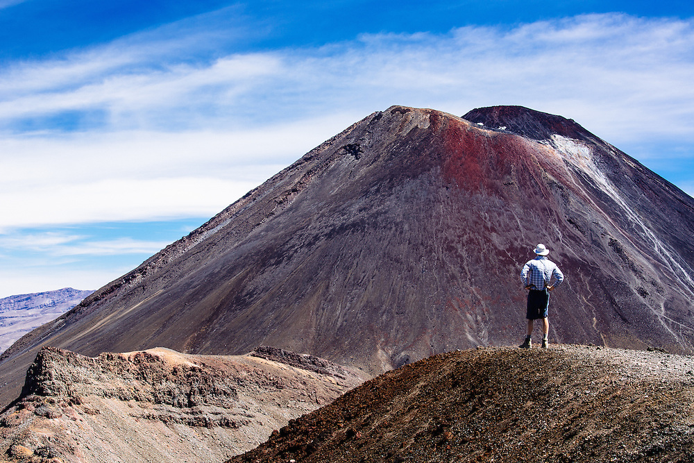 A walker stands solely in front of Mt Ngauruhow (also known as Mt Doom) along the Tongariro Alpine Crossing.