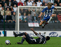 Photo: Dave Howarth.<br />Wigan Athletic v Bolton Wanderers. The Barclays Premiership. 02/10/2005. Graham Kavanah jumps out of the way of Radhi Jaidi