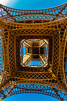 Looking up at the Eiffel Tower from directly underneath it. The world famous wrought-iron lattice tower is the most famous landmark of Paris, France.