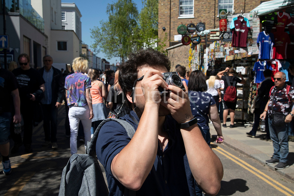 Man taking a picture with his digital camera on Portobello Road in Notting Hill, West London, England, United Kingdom. People enjoying a sunny day out hanging out at the famous Sunday market, when the antique stalls line the street.  Portobello Market is the worlds largest antiques market with over 1,000 dealers selling every kind of antique and collectible. Visitors flock from all over the world to walk along one of Londons best loved streets.
