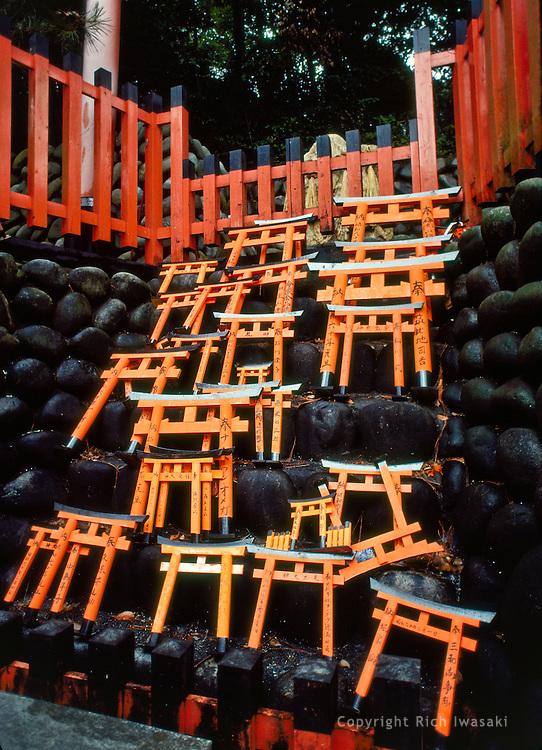 Wood torii (gates) stacked behind gravestones at Fushimi Inari-taisha (shrine), Kyoto, Japan