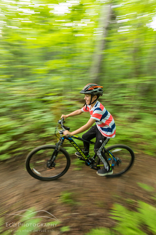 A boy rides his mountain bike on a trail near Deboullie Pond in Aroostook County, Maine. Deboullie Public Reserve Land.