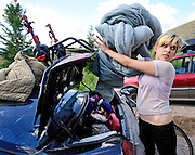 After a long day at work, Patience Melton, 21, unpacks her belongings at her favorite campsite in Curtis Canyon on Wednesday. The Florida native works at the Whole Grocer but has been unable to find housing.