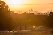 UNITED KINGDOM, London: 20 July 2020 <br /> Cyclists make their way through Richmond Park as the sun rises over the London skyline earlier this morning. The weather is set to be sunny in the capital city over the next few days.