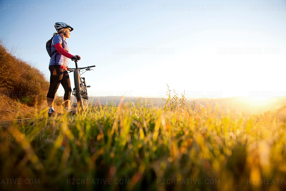 An active woman in her mid-twenties stands with a mountain bike watching the sunrise in southern California.