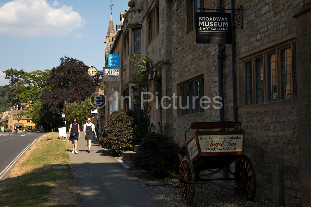 Broadway Museum and Art Gallery in The Cotswolds, United Kingdom. Broadway village lies beneath Fish Hill on the western Cotswold escarpment. The 'broad way' is the wide grass-fringed main street, centred on the Green, which is lined with red chestnut trees and honey-coloured Cotswold limestone buildings, many dating from the 16th century. It is known for its association with the Arts and Crafts movement, and is situated in an area of outstanding scenery and conservation. The wide High Street is lined with a wide variety of shops and cafes, many housed in listed buildings. The Cotswolds is an area in south central England. The area is defined by the bedrock of limestone that is quarried for the golden coloured Cotswold stone. It contains unique features derived from the use of this mineral; the predominantly rural landscape contains stone-built villages and historical towns.