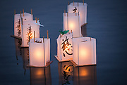 A group of paper lanterns, some with origami cranes affixed to the top, float in the waters of Green Lake during the annual From Hiroshima to Hope event, which observes the anniversary of the Hiroshima and Nagasaki atomic bombings. <br />