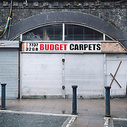 Budget Carpets. <br /> 22 Brixton Station Road.<br /> <br /> Raymond Murphy opened his business 25 years ago. In this side of his shop there is a small concession where 9 people work.